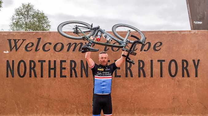 LONG WAY ROUND: Matt Muir raises his bike in triumph on his ride last year.