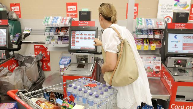 A customer uses a self-serve checkout at a Coles.