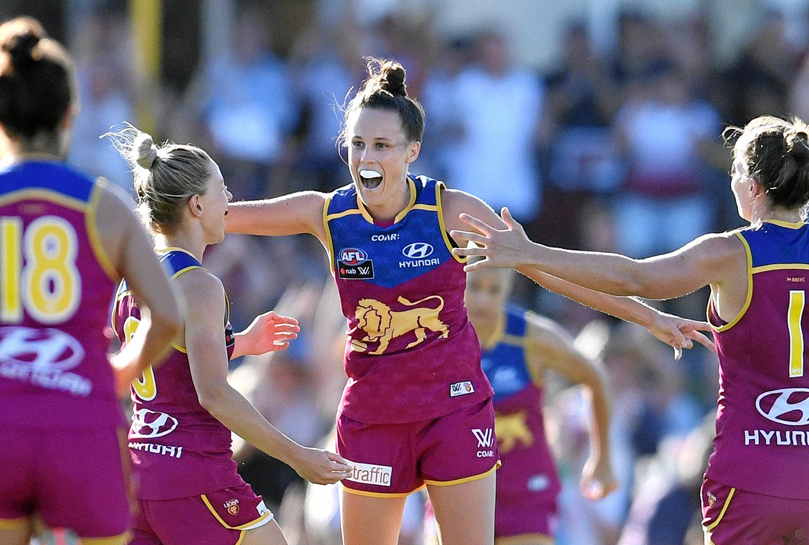 Emma Zeilke of the Brisbane Lions (centre) celebrates scoring a goal