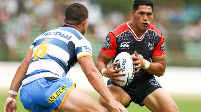 Roger Tuivasa-Sheck of the Warriors runs at Ash Taylor of the Titans.