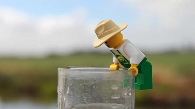 The Lego farmer checks the rain gauge after heavy falls.