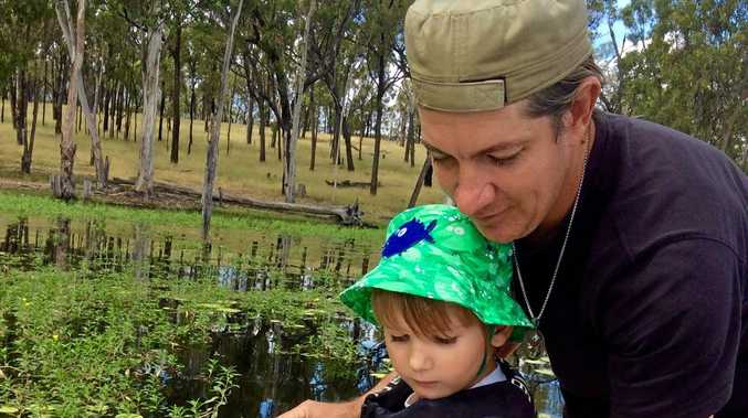 Hatchery Manager Kieron Galletly and Ollie Galletly releasing fingerlings into Eungella Dam.