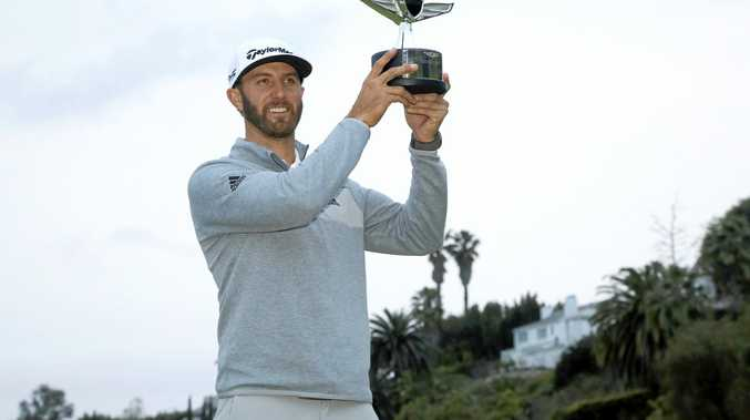 Dustin Johnson poses with his trophy on the 18th green after winning the Genesis Open golf tournament at Riviera Country Club.