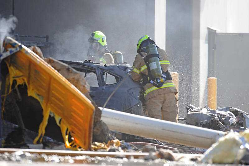 :Emergency services personnel are seen at the scene of a plane crash. Five people are believed to have been on board a light plane that crashed into a Melbourne factory outlet. (AAP Image/Joe Castro)