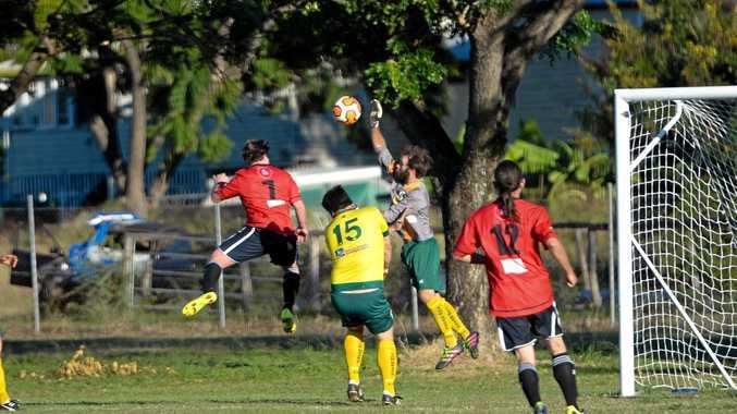 Goalie Michael Hogarth saves the ball from Michael Moore in the Berserker V Emerald Eagles soccer game at Elizabeth Park on June 26, 2016. Photo Trinette Stevens / Morning Bulletin