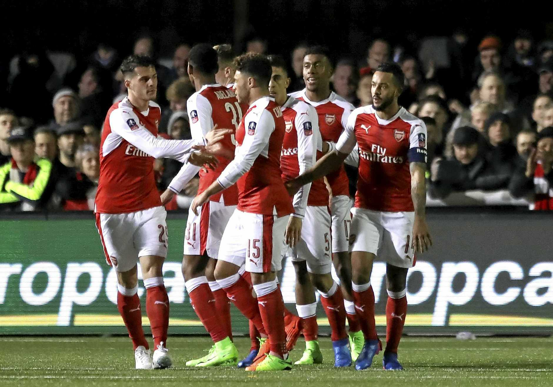 Arsenal's players celebrate Theo Walcott's, right, goal during the English FA Cup fifth round soccer match against Sutton United at Gander Green Lane stadium in London