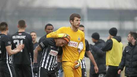 Partizan Belgrade's Brazilian player Everton Luiz, centre left, leaves the field accompanying by goalkeeper Filip Kljajic