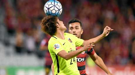 Takahiro Sekine (left) of the Red Diamonds competes for the ball with Mario Shabow of the Wanderers