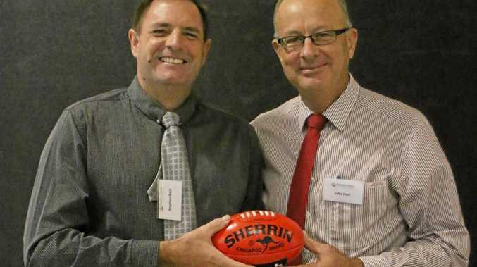 Stephen Reid and John Hart holding their football at the Brisbane Lions Mayor's Breakfast.