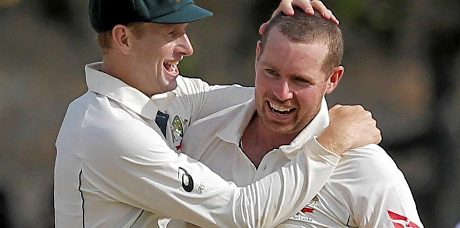 Australia's Jon Holland (right) is congratulated by Adam Voges after taking a wicket against Sri Lanka.