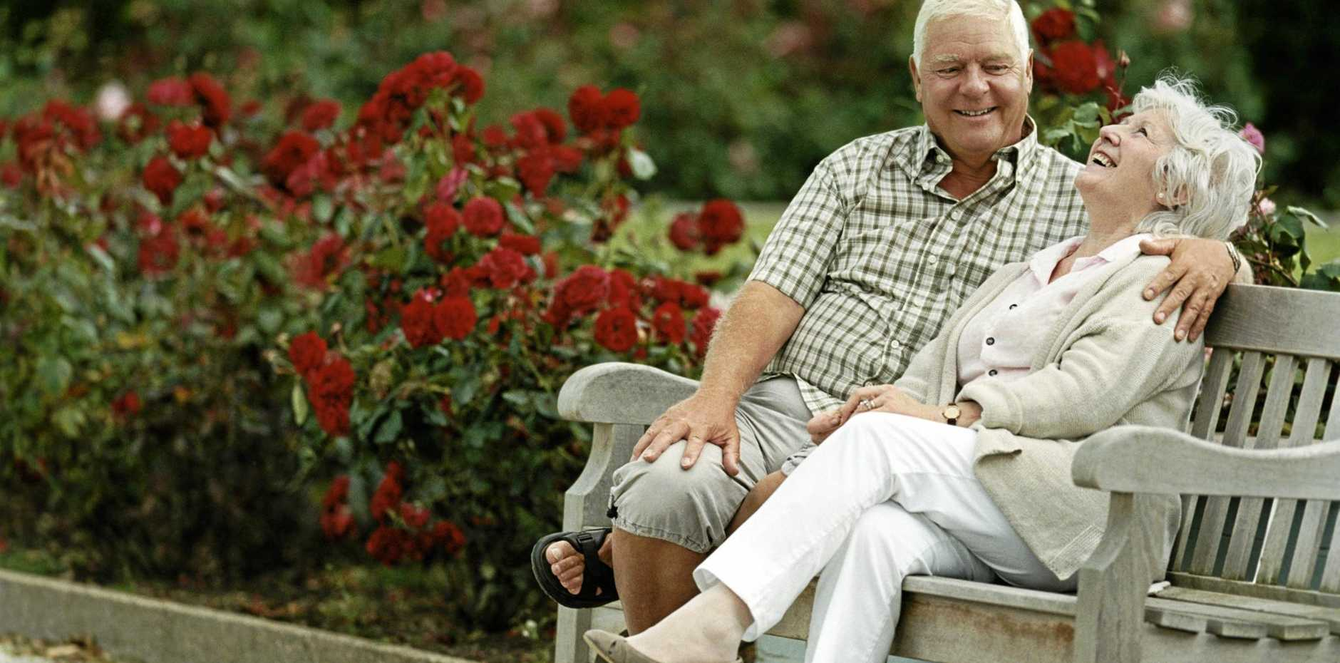 A Senior Couple Sitting on a Park Bench, enjoying each other company.