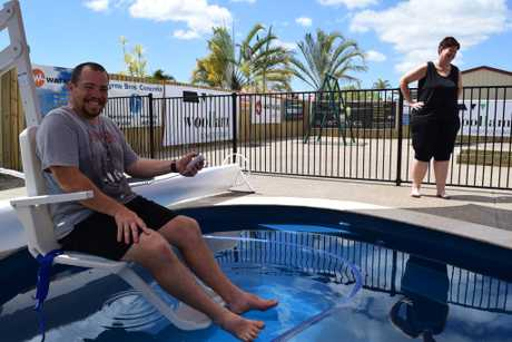 TRANSFORMED: Cameron Harris sits in his son Aedan's new chair lift, while Donna Harris looks over the new backyard created by Fraser Coast businesses.