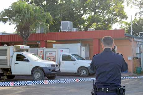 Police take photos of the crime scene after an armed robbery at Mother's Pantry, Connors Road, Paget.