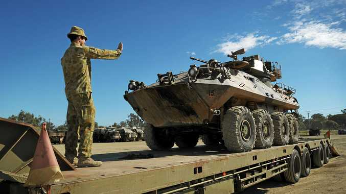 Crew Commander Lance Corporal Andrew Jackson of 2 Cavalry Regiment in Darwin guides an Australian Light Armoured Vehicle (ASLAV) onto a flatbed truck prior to transport from Defence Service Group to Rockhampton.