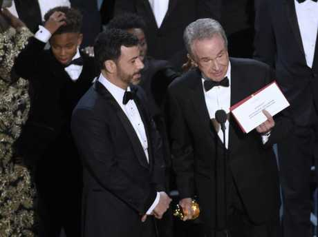 Presenter Warren Beatty shows the envelope with the actual winner for best picture as host Jimmy Kimmel, left, looks on at the Oscars on Sunday, Feb. 26, 2017, at the Dolby Theatre in Los Angeles. The winner was originally announced as La La Land, but was later corrected to Moonlight.
