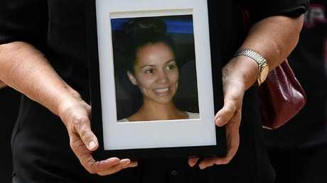 A supporter of Tara Brown's family holds a photo of the murdered woman outside court in Brisbane today. Picture: Dan Peled/AAP
