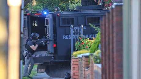Police use an armoured vehicle to break down a gate at the home. Picture: Hamish Blair Source:News Corp Australia