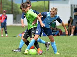 Crusader FC Under 12 player Logan Harmer fights for the ball aginst Townsville.