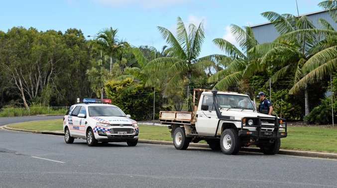 Police question a man at Mackay Harbour yesterday afternoon.