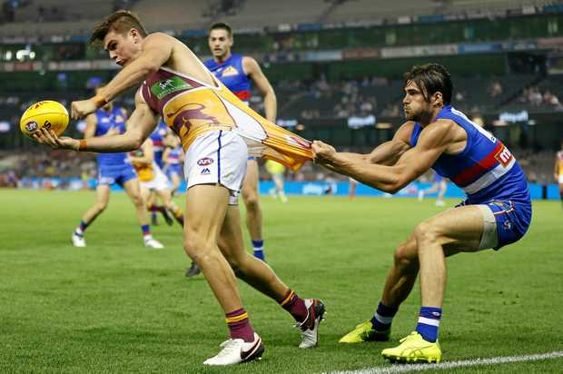 Ben Keays of the Lions is tackled by Easton Wood of the Bulldogs  at Etihad Stadium