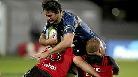 Brumbies Sam Carter, centre, attempts to bust the tackle of Crusaders Codie Taylor and Owen Franks, right, during their Super Rugby match in Christchurch