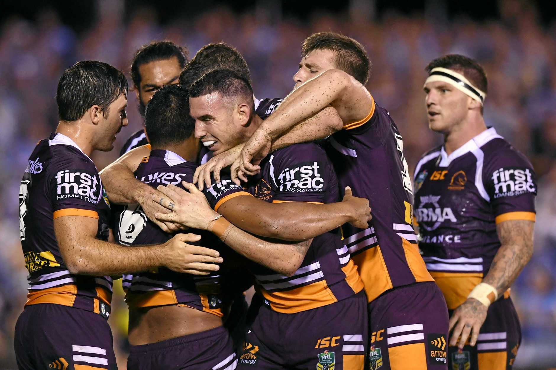 Anthony Milford (2nd left) of the Broncos is congratulated after scoring a try  at Southern Cross Group Stadium in Sydney on Thursday
