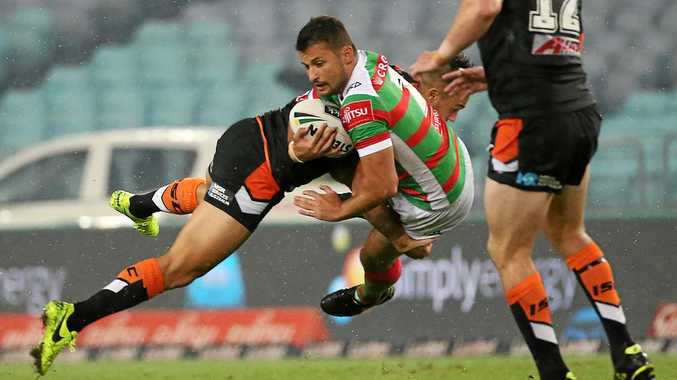 Luke Kelly of the Rabbitohs is tackled by Luke Brooks of the Tigers.