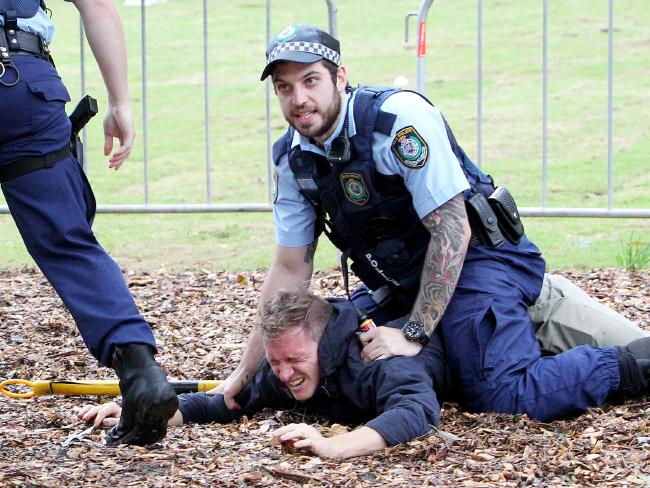 A police officer subdues a man.