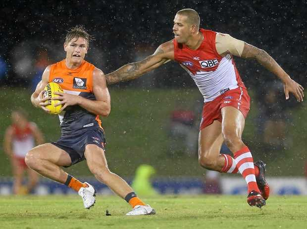 Adam Tomlinson of the Giants is tackled by Lance Franklin of the Swans.