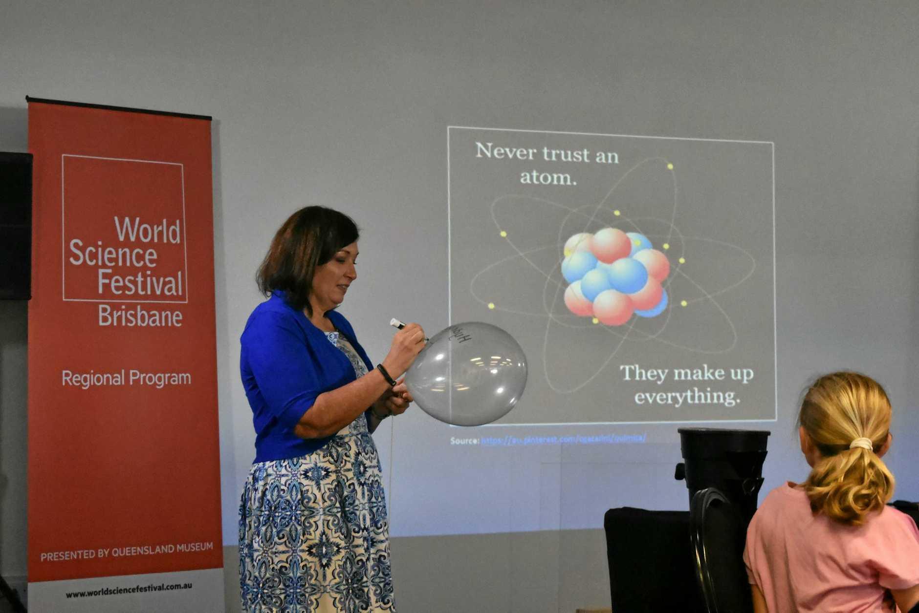 Science Minister Leeanne Enoch helps demonstrate how a Hydrogen atom works.