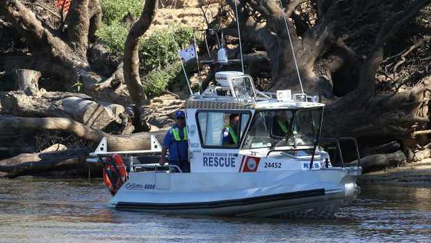A marine rescue boat from NSW searches the Murray for the missing five-year-old. Picture: Hamish Blair
