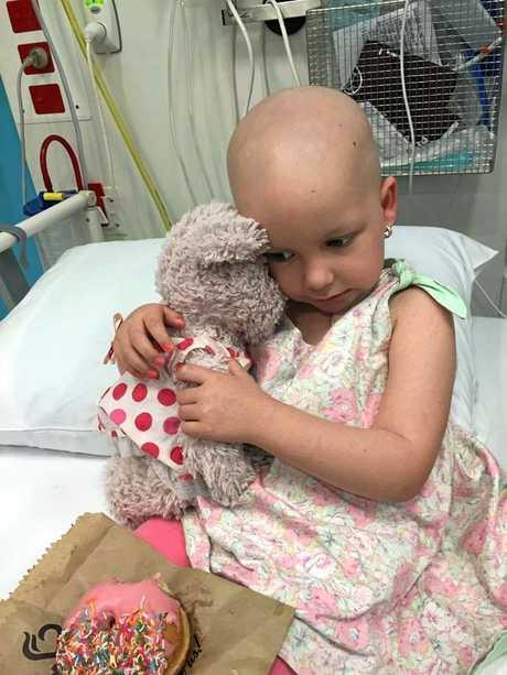 Elki Guymer cuddles a teddy during treatment.