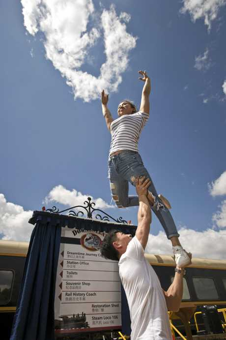 Zhang Shuo lifts Zhao Chujing of Wuqiao Acrobatic Troupe in front of a new bilingual sign at DownsSteam Tourist Railway and Museum, Tuesday, March 7, 2017.