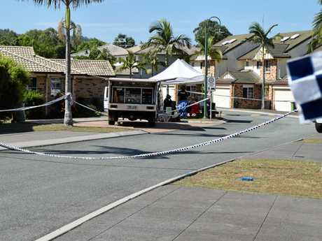CRIME SCENE: Police scour a murder scene on College Rd at Karana Downs.