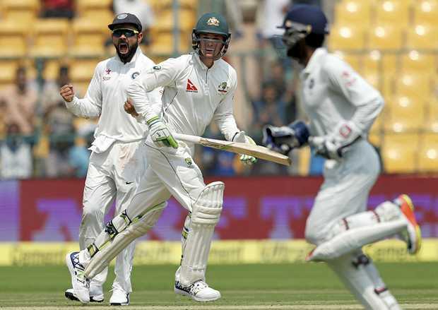 India's captain Virat Kohli, left, celebrates the dismissal of Australia's Peter Handscomb