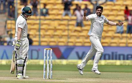 India's Umesh Yadav, right, celebrates the dismissal of Australia's captain Steven Smith