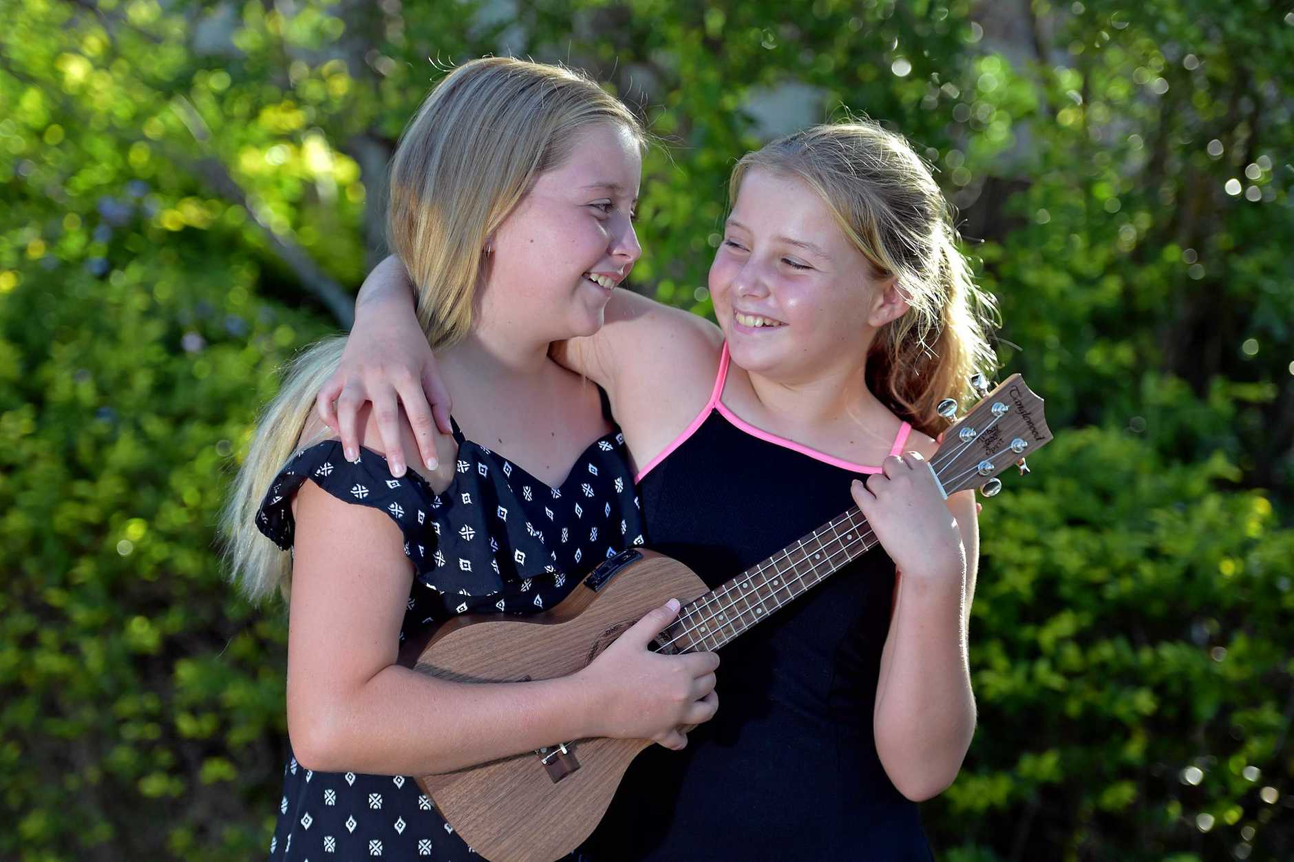 Trini Blackmore,12, has discovered she loves to sing and play the ukulele.Twin sister Madi (right) joins in the fun.