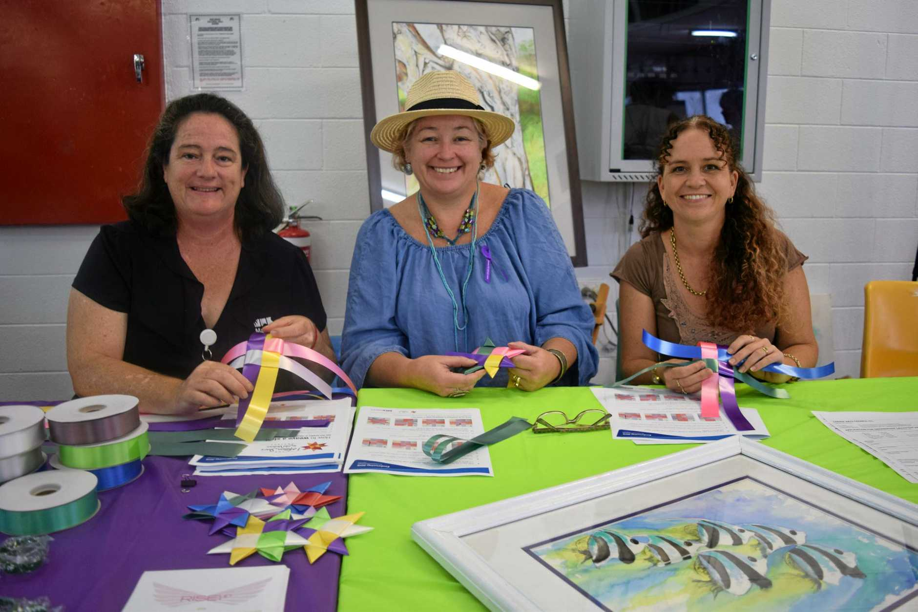 HELPING HANDS: Fiona Vuibeqa, Tracey Daws and Jodie Perna help weave 1 million stars .