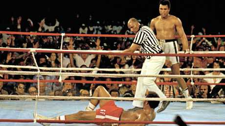 Muhammad Ali (right) stands back as referee Zack Clayton calls the count over opponent George Foreman.