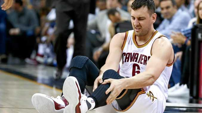 Andrew Bogut holds his leg after breaking it.
