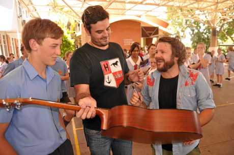 RGS past student Tom Bubsy and Busby Marou manager, Joshua Jones (centre) looks on as James Freeman has his guitar signed. Photo Contributed