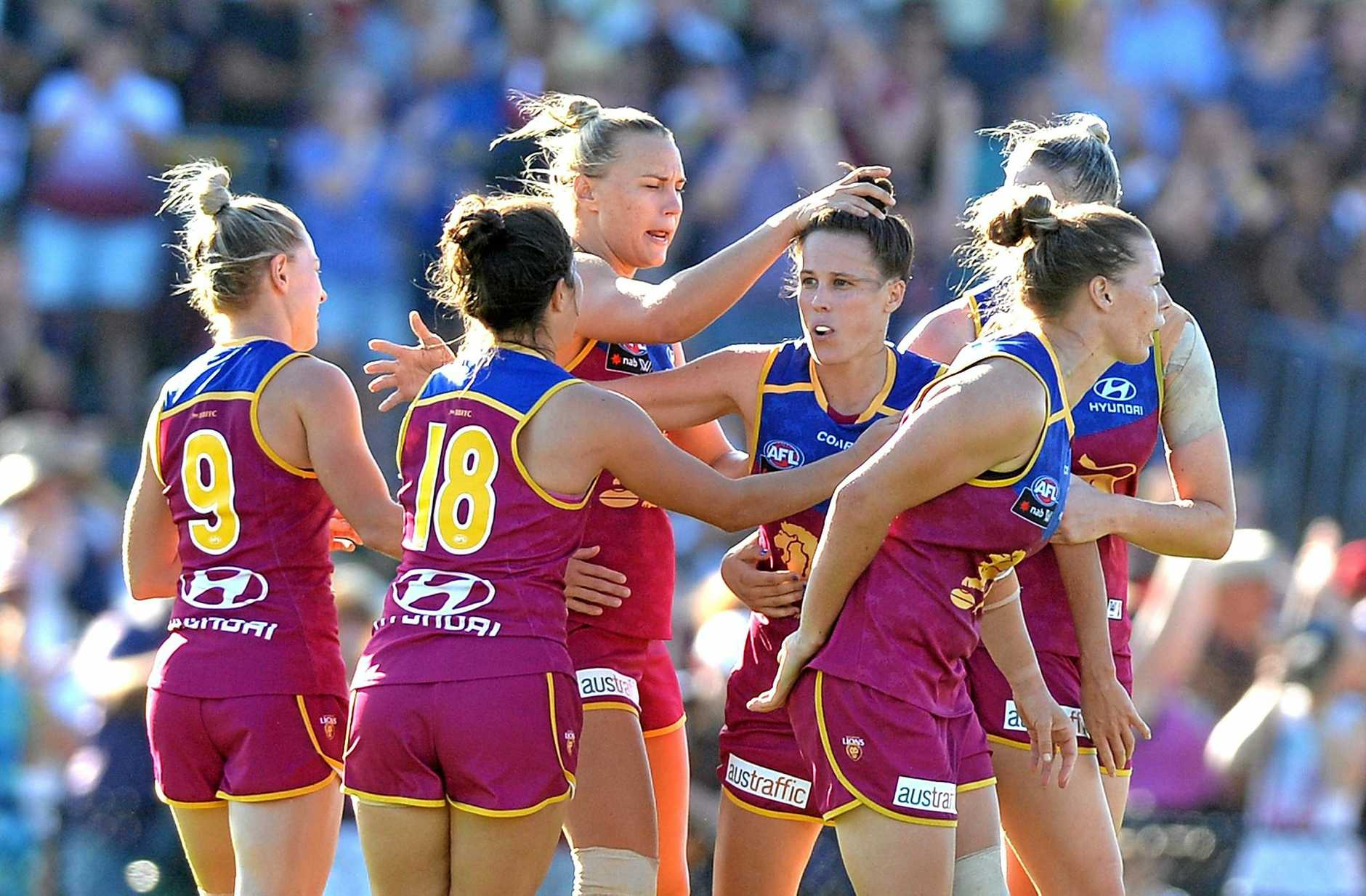 BRISBANE, AUSTRALIA - FEBRUARY 18:  Emma Zielke of the Lions is congratulated by team mates after kicking a goal during the Women's AFL round three match between the Brisbane Lions and the Collingwood Magpies at South Pine Sports Complex on February 18, 2017 in Brisbane, Australia.  (Photo by Bradley Kanaris/AFL Media/Getty Images)