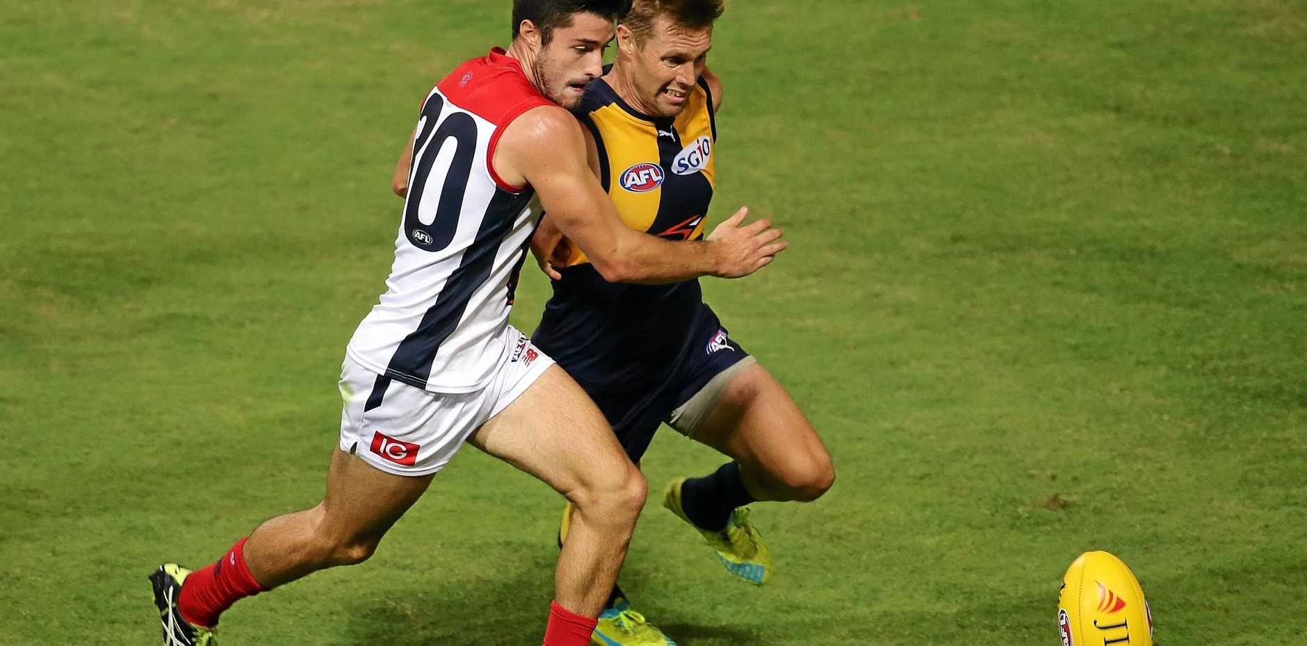Colin Garland of the Demons and Sam Mitchell of the Eagles chase the ball.