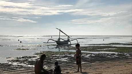 FAMILY FUN: Kids have fun exploring the beach at Sanur at low tide.