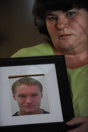 Helen Gordon with a portrait of her son Leonard Gordon, who was murdered at Maryborough Correctional Centre.