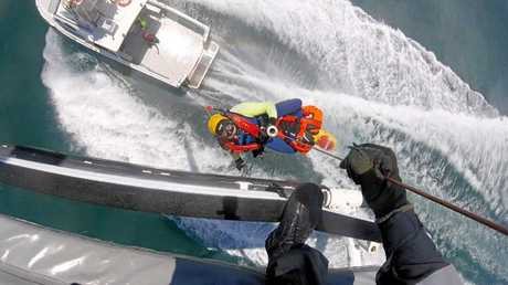 RESCUE MISSION: Crewman being winched onto the back of a vessel at Mackay Harbour port.