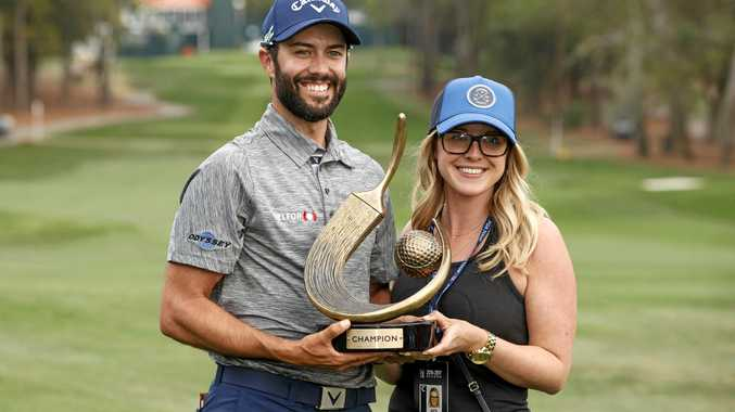 Adam Hadwin and his fiance Jessica Kippenberger hold up the champion's trophy after he won the Valspar Championship.