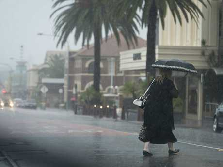 A pedestrian crosses Neil St as heavy rain falls in Toowoomba, Tuesday, March 14, 2017.