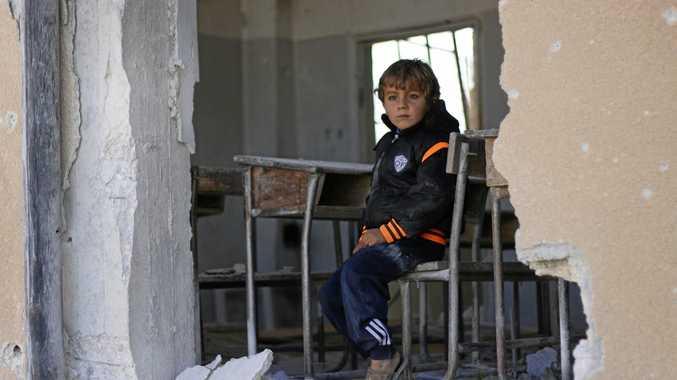 A Syrian boy Ahmed, 6, sits in a damaged school classroom, in Idlib, north Syria.