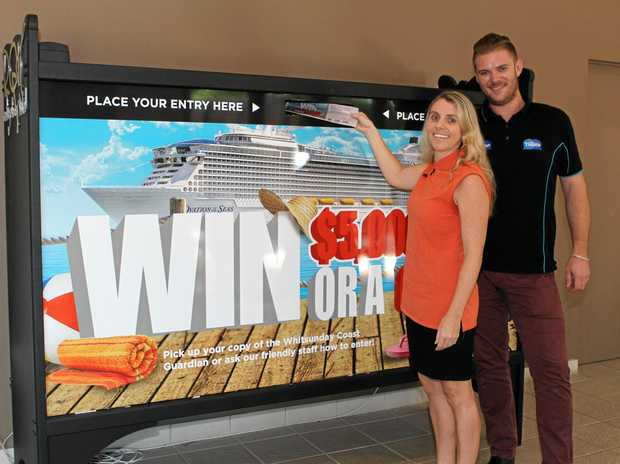 IN IT TO WIN IT: Hayley Cummings places a competition entry alongside Whitsunday Times GM Steven Jacklin.